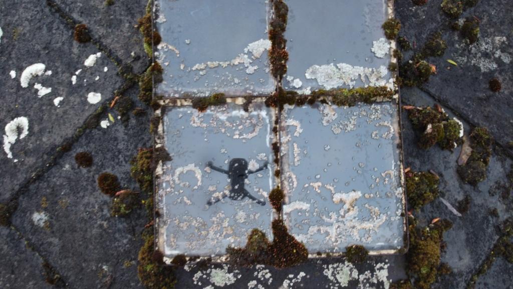 Ein Dachfenster, alles ziemlich verwittert und mit Moos und Flechten bewachsen, in dem sich eine Drohne spiegelt
